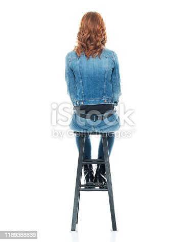 Rear view / back / one person / full length of 20-29 years old adult beautiful redhead / long hair caucasian female / young women sitting / resting / relaxing wearing double denim / jeans / pants / denim jacket / boot / rolled-up sleeves / jacket / warm clothing / sitting on stool