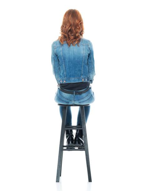 Rückansicht / Rücken / eine Person / volle Länge von 20-29 Jahre alt Erwachsene schöne Rotschopf / lange Haare kaukasische frau / junge Frauen sitzen / ruhen / entspannend / sitzen auf Hocker – Foto