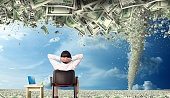 conceptual finance image of rear view businessman sitting on chair with laptop computer looking at money covered view with storm of money tornado