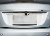 Rear view camera is hidden on the license plate behind the sedan car.