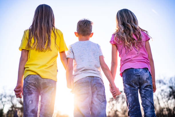 Rear view children holding hands stock photo