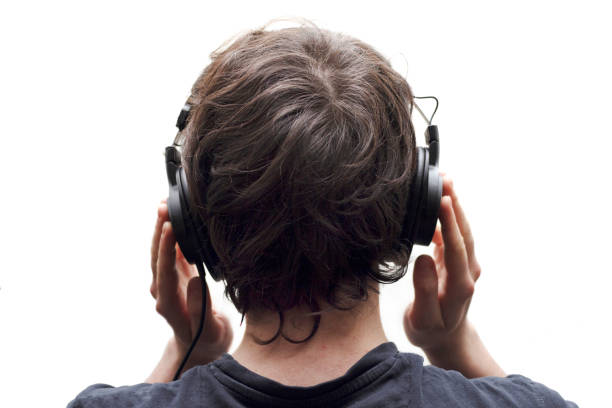 Rear view closeup of young man listening to music with stereo headphones on white background. stock photo