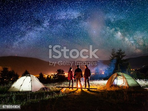 678554980 istock photo Rear view couple hikers standing near campfire in the camping 678554904