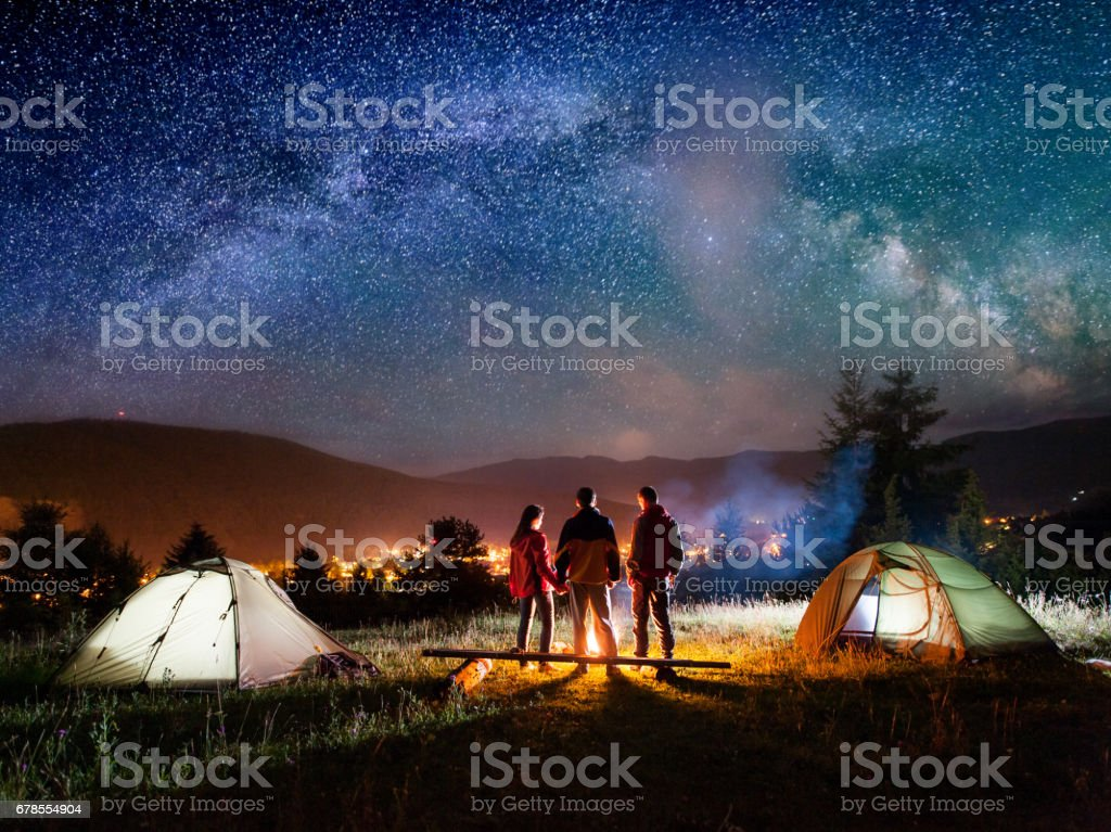 Rear view couple hikers standing near campfire in the camping stock photo