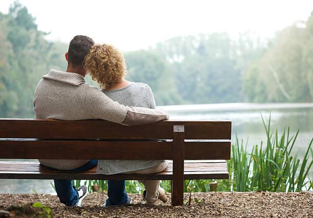vista traseira casal sentado no banco ao ar livre - banco assento - fotografias e filmes do acervo