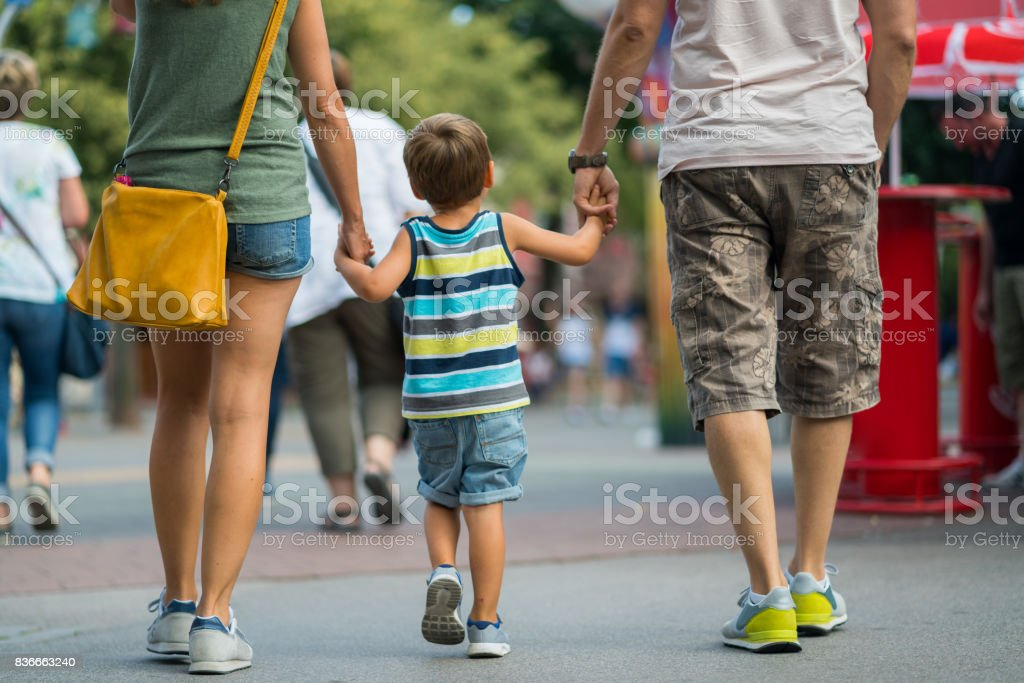 rear view family walking together on summer day in amusement park stock photo