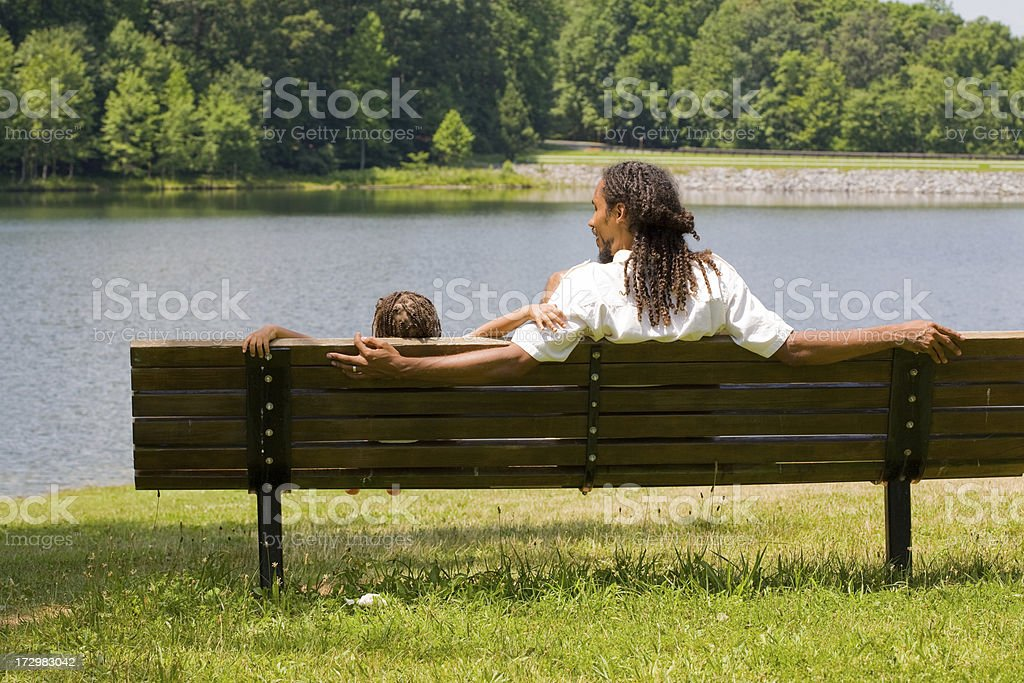 Rear view, father and son on a bench at lakeside royalty-free stock photo