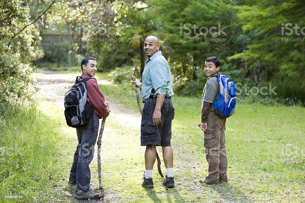 Rear view father and sons hiking in woods on trail royalty-free stock photo
