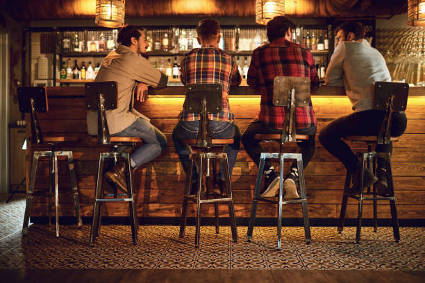Rear view friends sitting on chairs talking at the bar in a bar. stock photo