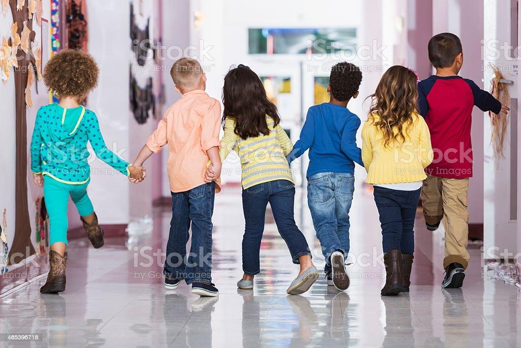 Rear view, group of preschoolers walking down hallway stock photo