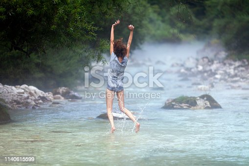 Rear View Happy Adult Woman Jumping in the Air in the Middle if the River