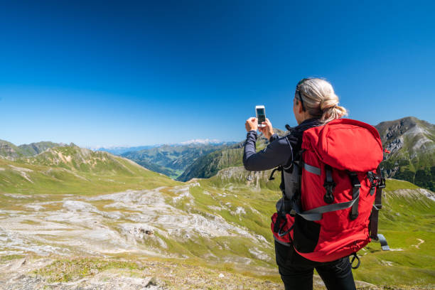 rear view hiker woman taking picture of mountain panorama at clear blue sky stock photo