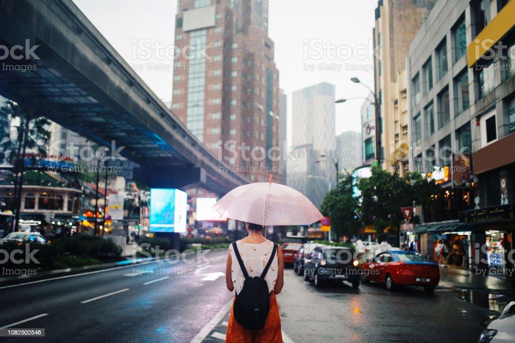 Rear view image of a solo traveler woman in Kuala Lumpur, Malaysia stock photo