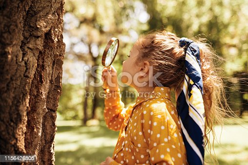 istock Rear view image of cute little girl exploring the nature with magnifying glass outdoor. Child playing in the forest with magnifying glass. Curious kid looking through magnifier to the tree in the park 1156426805