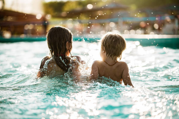 Rear view little boy and girl sitting and splashing in the pool Rear view kids enjoying splashing in the pool swimming pool stock pictures, royalty-free photos & images