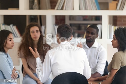 511741068 istock photo Rear view man sharing problems with diverse group at therapy 1172962733
