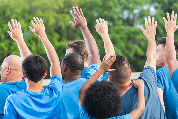 Rear view multi-ethnic group of volunteers raising hands stock photo