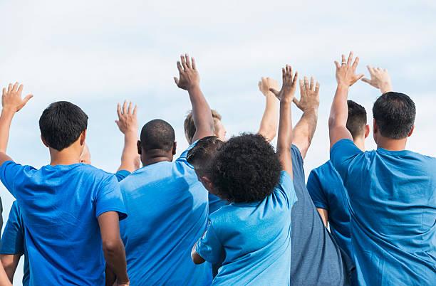 Rear view multi-ethnic group of volunteers raising hands stock photo