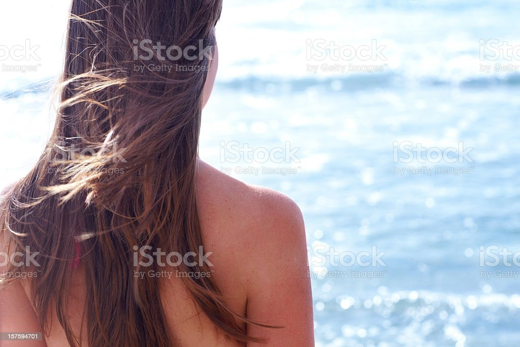 Rear view of a attractive  young woman by the sea stock photo