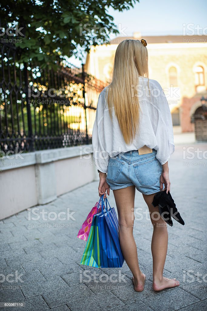 Rear view of a barefoot woman standing with shopping bags. zbiór zdjęć royalty-free