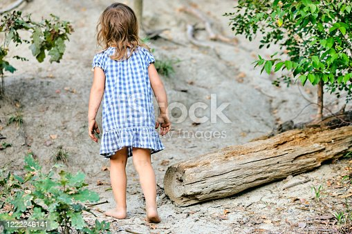 Rear view of a barefooted 3 year old child girl in a summer dress walking in the forest. Seen in Germany in August.