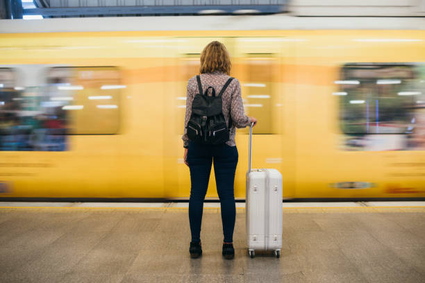 Rear view of a blond woman waiting at the train platform Rear view of a blond woman waiting at the train platform railroad station platform stock pictures, royalty-free photos & images