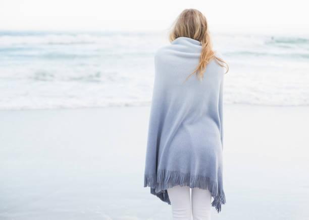 vista trasera de una mujer rubia calentando en una manta - chica rubia espaldas fotografías e imágenes de stock