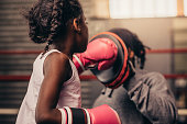 Girl wearing boxing gloves straining with her coach. Boxing kid practicing punches on a punching pad with her coach.