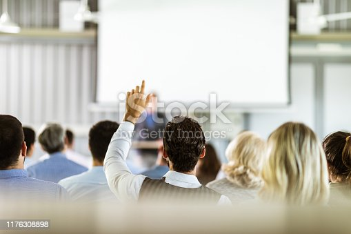 istock Rear view of a businessman asking a question on seminar in board room. 1176308898
