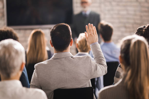 Rear view of a businessman raising his hand on a seminar in a board room. stock photo