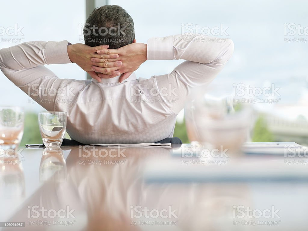 Rear view of a businessman relaxing with hands behind head royalty-free stock photo