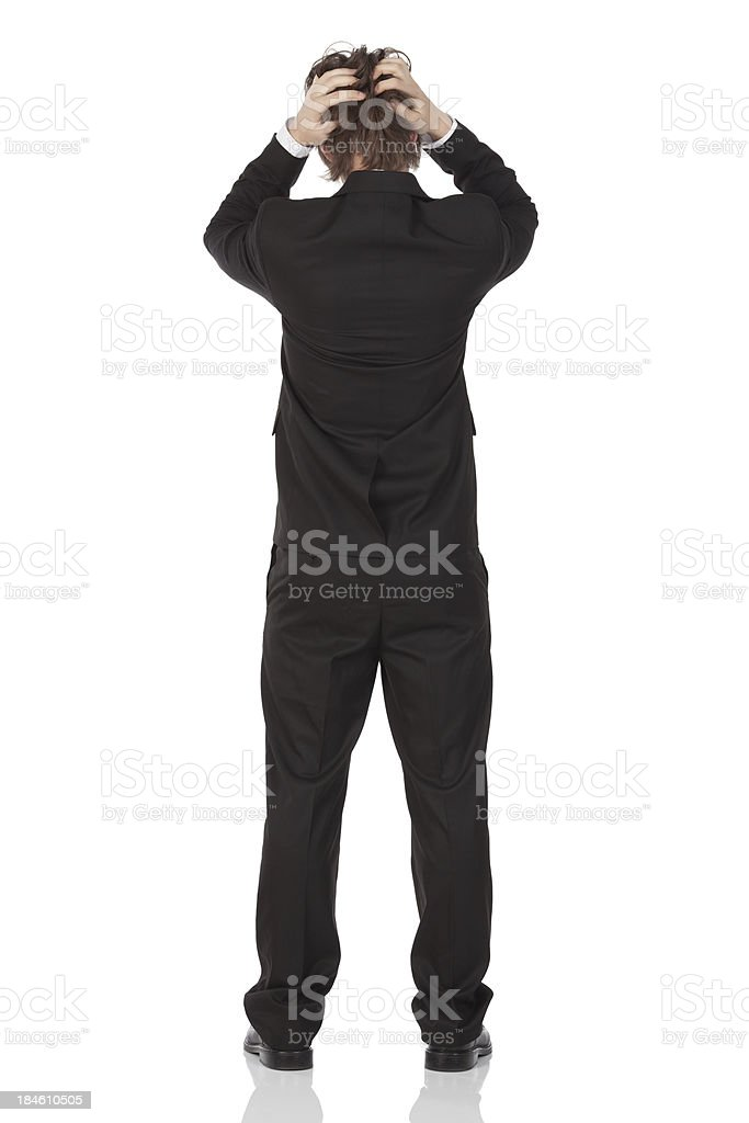 Rear view of a businessman scratching his hair stock photo