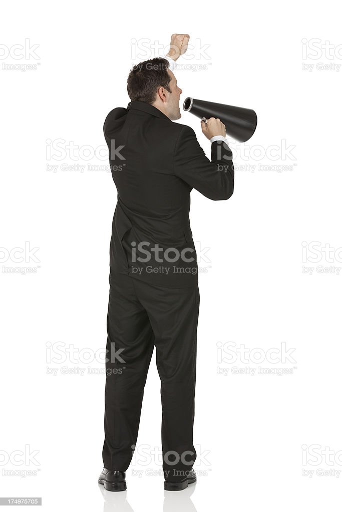 Rear view of a businessman shouting into a bullhorn royalty-free stock photo