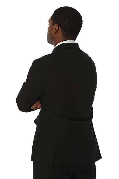 Rear view of a businessman standing with arms crossed stock photo
