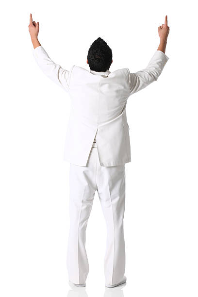 rear view of a businessman standing with arms raised - white suit stock photos and pictures