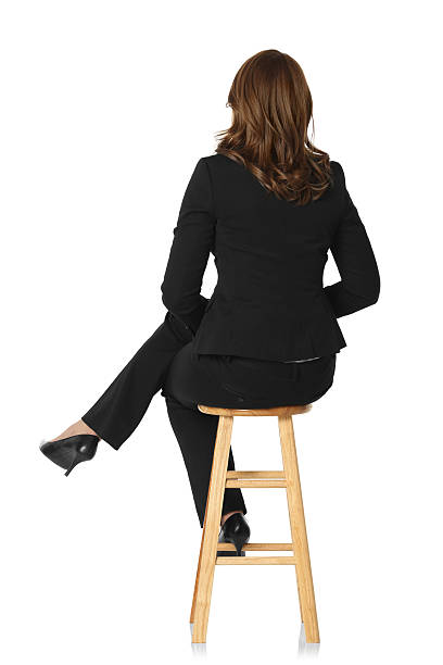 Rear view of a businesswoman sitting on stool stock photo