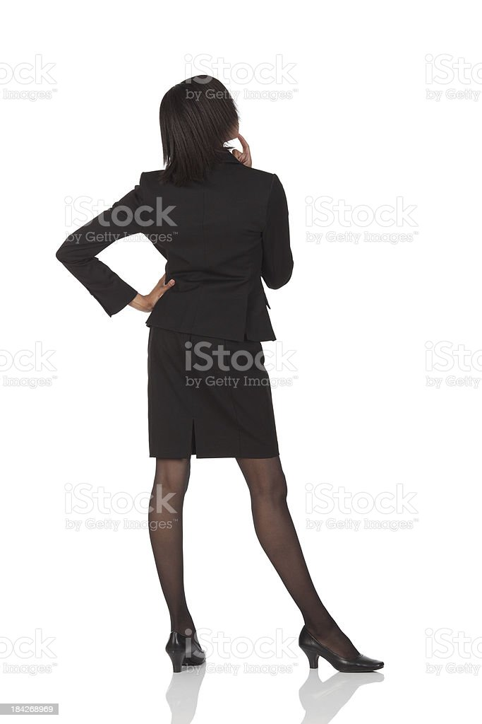 Rear view of a businesswoman standing in thoughtful pose stock photo