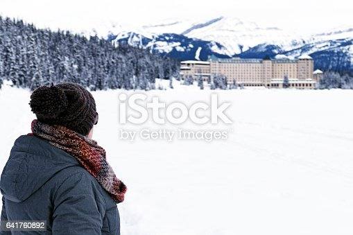 istock Rear view of a caucasian woman with winter clothing , looking at the Fairmont Chateau Lake Louise,Banff National Park,Alberta,Canada 641760892