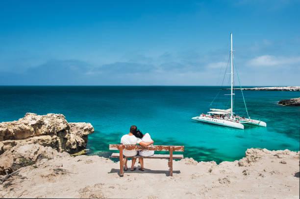 heckansicht des ein liebespaar im urlaub. honeymoon reisende paar umarmt auf einer holzbank und genießt ihren tropischen urlaub. hochzeit reise. junge brautpaar sitzt wieder am strand. reisende - hochzeitsreise zypern stock-fotos und bilder
