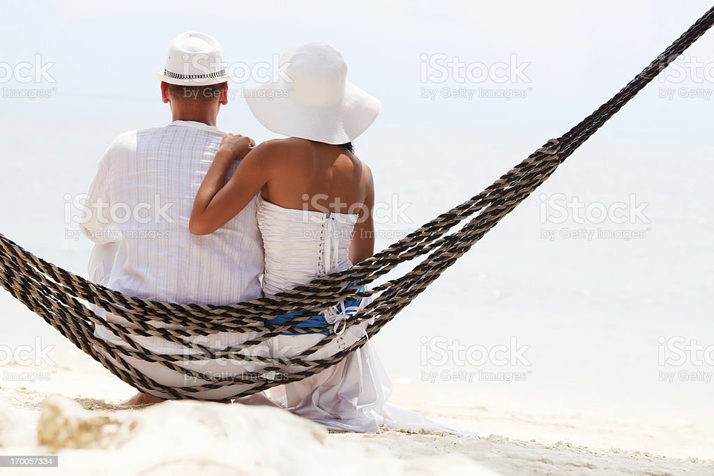 Rear view of a couple sitting on swing royalty-free stock photo