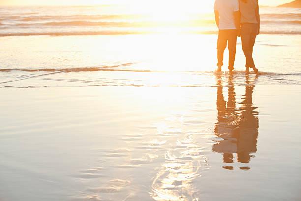 vista posteriore di una coppia in piedi insieme sulla spiaggia a - spiaggia coppia amore foto e immagini stock