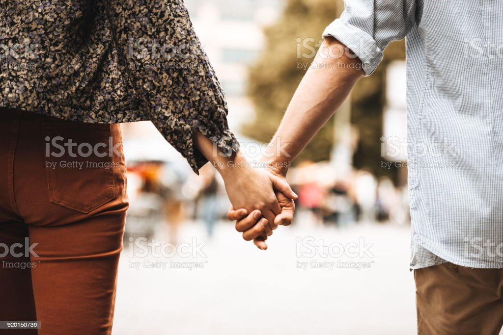 rear view of a couple walking on the street stock photo