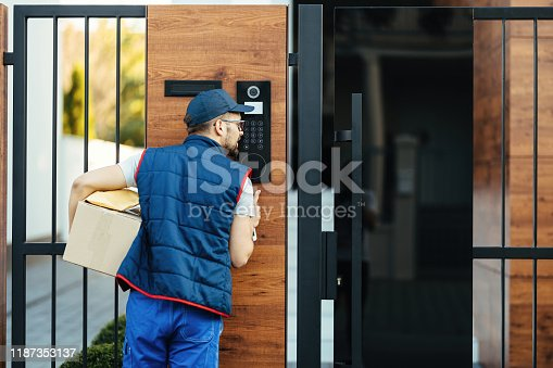 Back view of a deliverer ringing on intercom at gate of a customer's house while delivering packages.