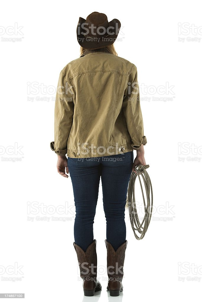 Rear view of a cowgirl standing with lasso royalty-free stock photo