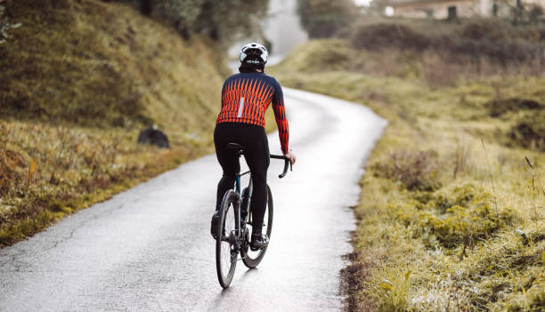 rear view of a cyclist in the countryside stock photo