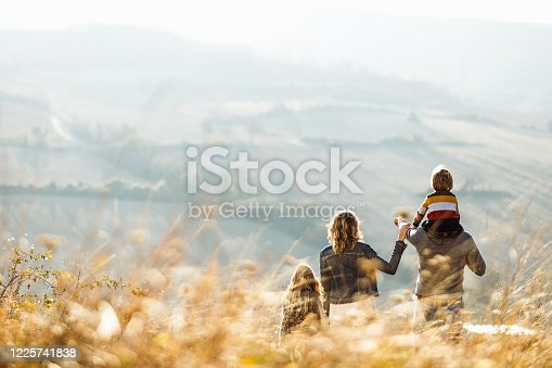 Back view of a family standing on a hill in autumn day while father is aiming at distance. Copy space.