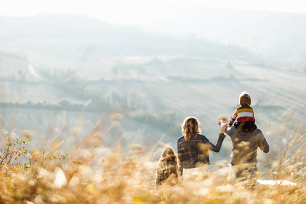 Rear view of a family standing on a hill in autumn day. stock photo