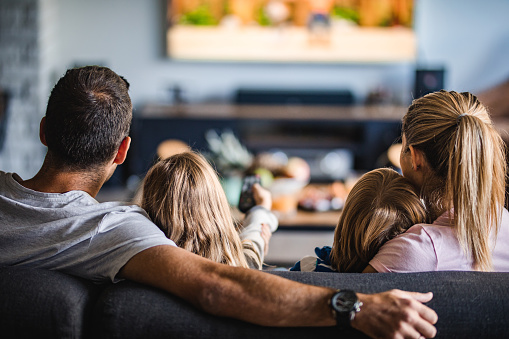 Back view of a relaxed family watching TV on sofa in the living room.