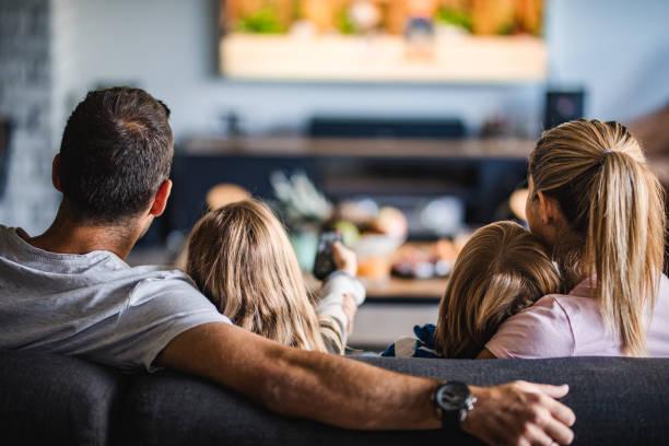 vista posteriore di una famiglia che guarda la tv sul divano a casa. - family foto e immagini stock