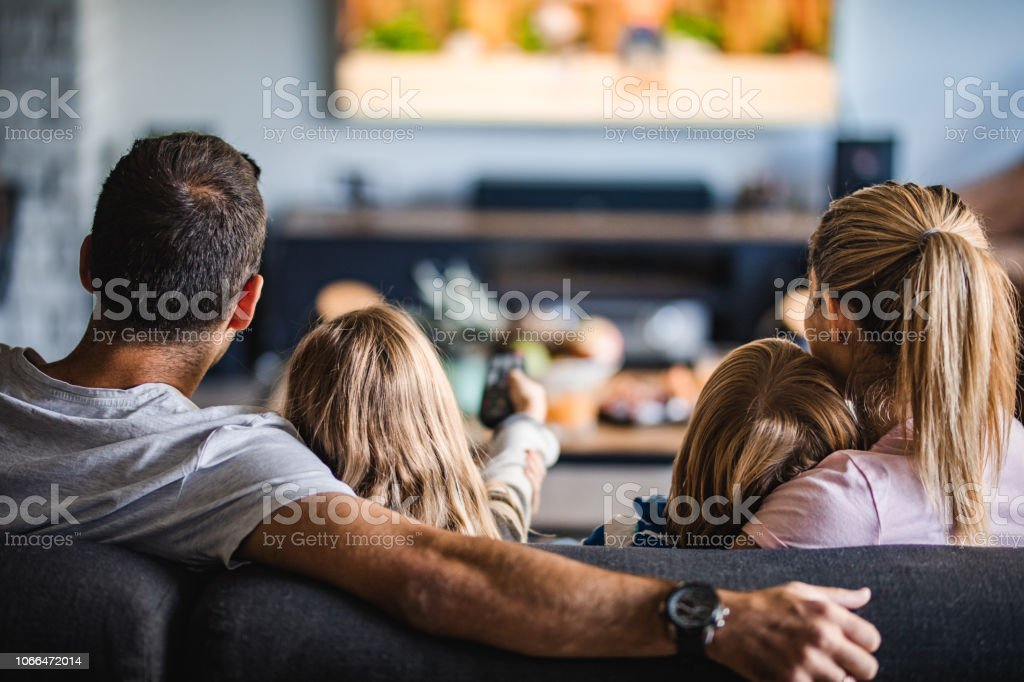 Rear view of a family watching TV on sofa at home. stock photo